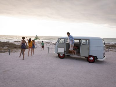 Side view of a Caucasian man getting down of a camper van against his friends walking towards beach
